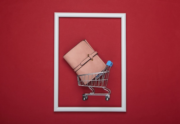 Einkaufswagen mit lederbrieftasche in einem weißen rahmen auf roter oberfläche