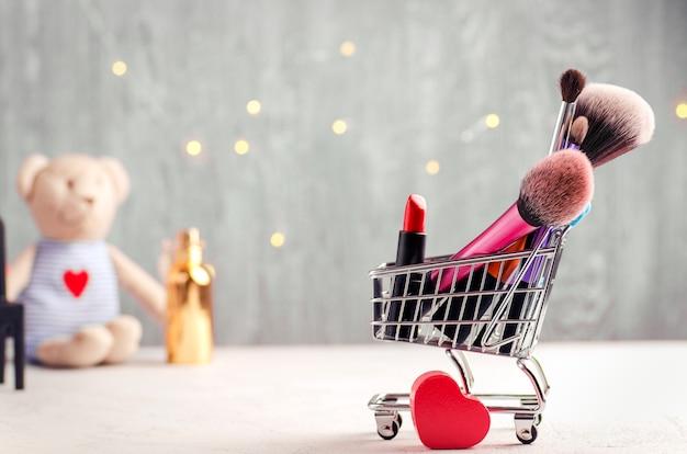 Einkaufswagen mit make-upbürsten, rotem lippenstift und herzform. teddybär- und feenlichterhintergrund