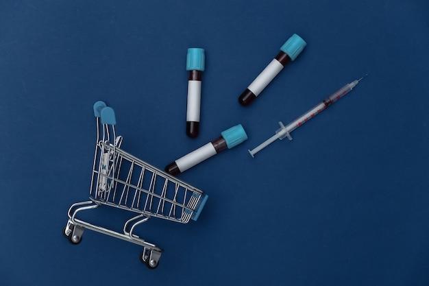 Einkaufswagen mit medizinischen reagenzgläsern, spritze auf klassischem blauem hintergrund. ansicht von oben