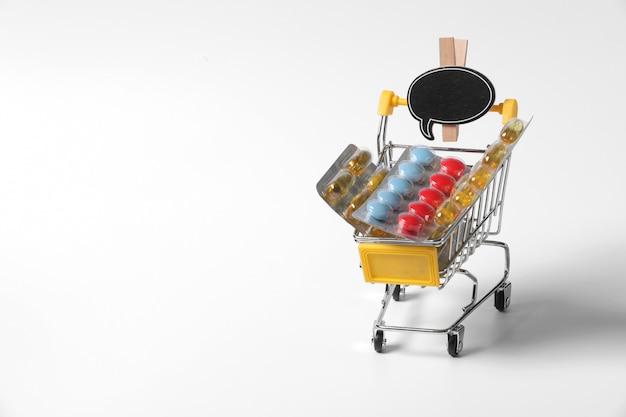 Einkaufswagen mit medizinischen vorräten lokalisiert auf weißer wand. medizin im korb. verkauf von medikamenten.