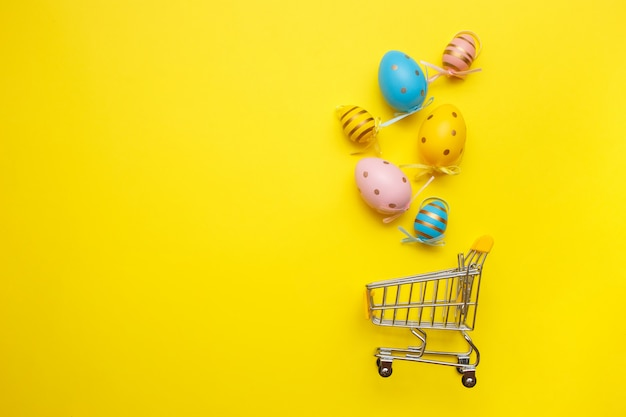 Einkaufswagen mit ostereiern auf gelb