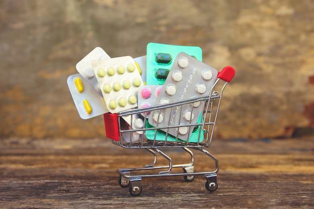 Einkaufswagen mit pillen auf altem holztisch.
