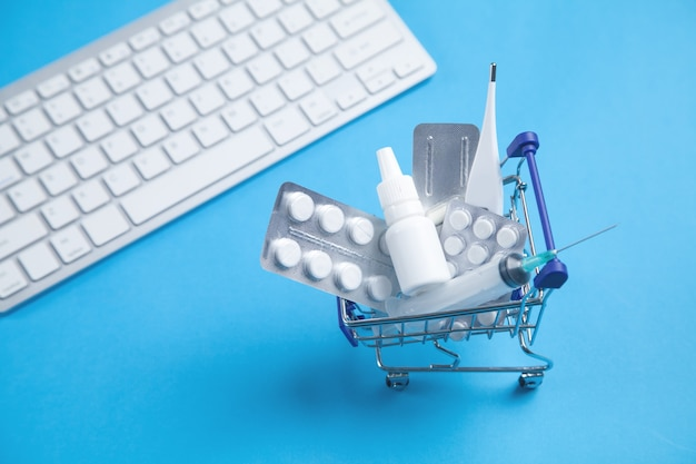 Einkaufswagen mit pillen, medizinischer flasche, thermometer, spritze und tastatur auf blauem hintergrund.