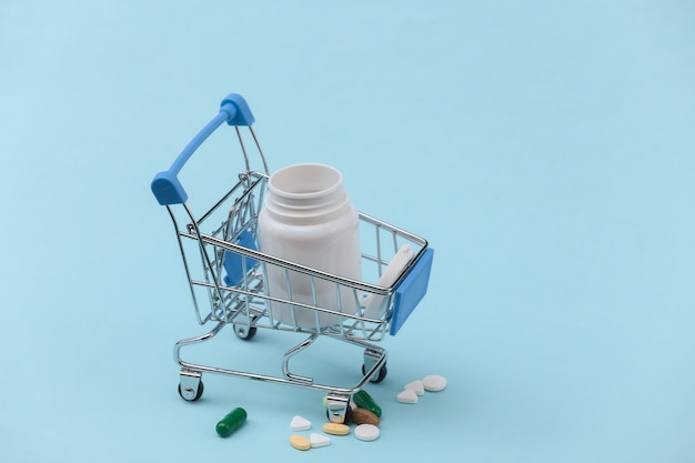 Einkaufswagen mit pillenflasche auf blauem grund.