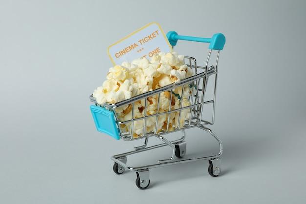 Einkaufswagen mit popcorn und ticket auf hellgrauem hintergrund.