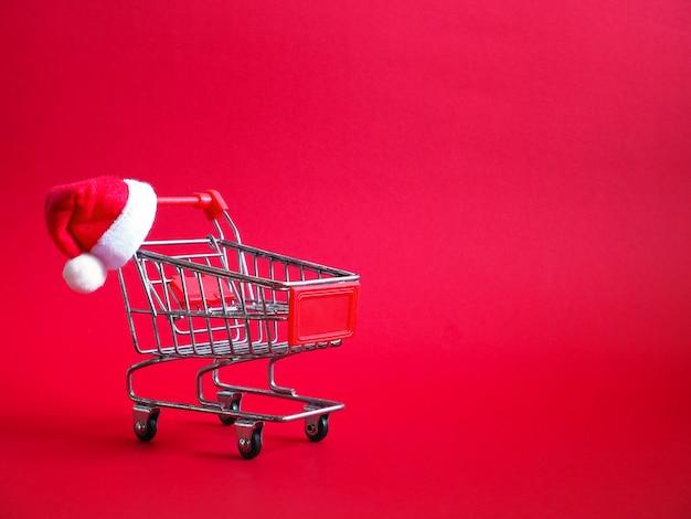Einkaufswagen mit rotem weihnachtsmann-hut auf rot