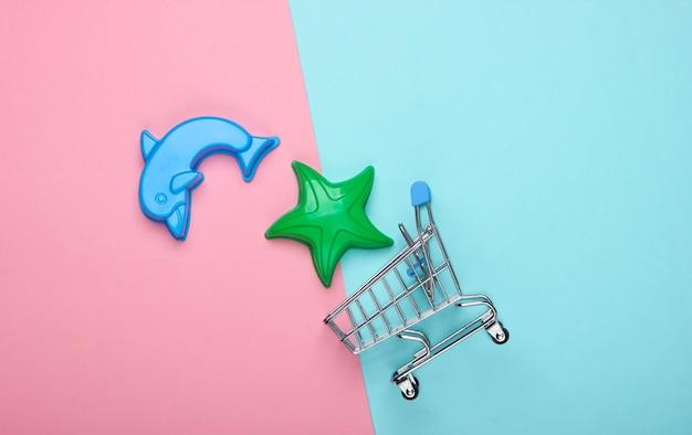 Einkaufswagen mit spielzeugformen für den sand auf einem blau-rosa pastell