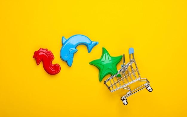Einkaufswagen mit spielzeugformen für den sand auf gelb