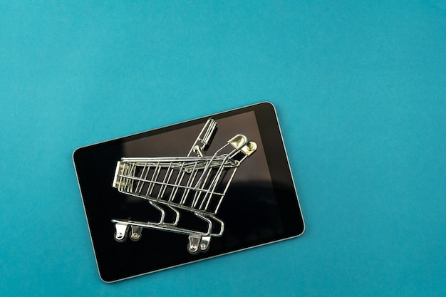 Einkaufswagen mit tablette lokalisiert auf blauem hintergrund, geschäftseinkaufs-online-konzept.