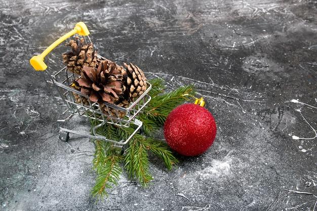 Einkaufswagen mit tannenzapfen, weihnachtskugel und tannenzweigen daneben, dunkler strukturierter hintergrund, neujahrshintergrund, kopierraum