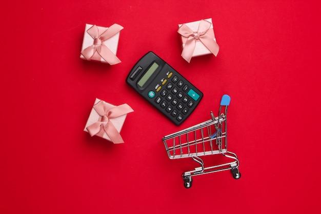 Einkaufswagen mit taschenrechner, geschenkboxen auf rot.