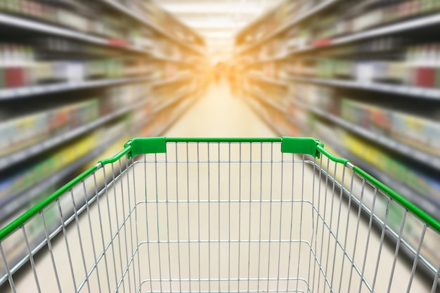 Einkaufswagen mit unschärfehintergrund von weinflaschen auf alkoholregalen im supermarktgeschäft