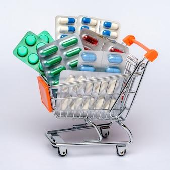 Einkaufswagen mit voller medizinischer pillen oder vitamine über hellgrauem hintergrund