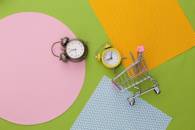 Einkaufswagen mit wecker auf kreativem buntem papierhintergrund.