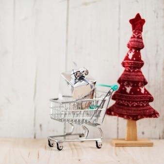 Einkaufswagen mit weihnachtsgeschenk und baum