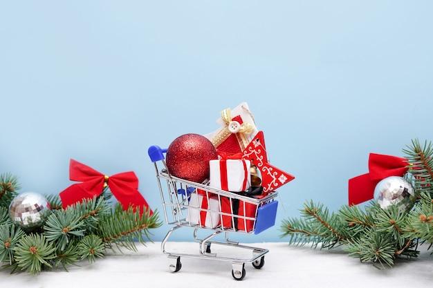 Einkaufswagen mit weihnachtsgeschenkboxen und -dekorationen auf blauem hintergrund. weihnachts- und neujahrsverkauf.