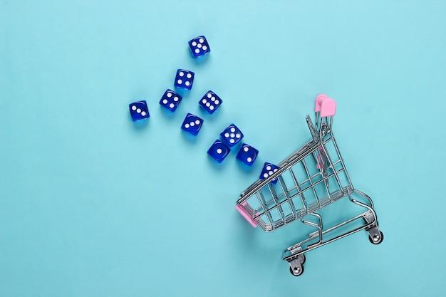Einkaufswagen mit würfeln auf einem blauen pastellhintergrund. viel glück beim einkaufen. draufsicht