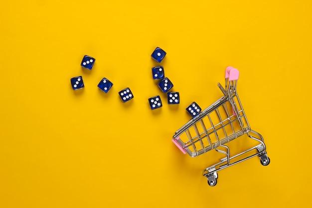 Einkaufswagen mit würfeln auf gelbem hintergrund. viel glück beim einkaufen. draufsicht