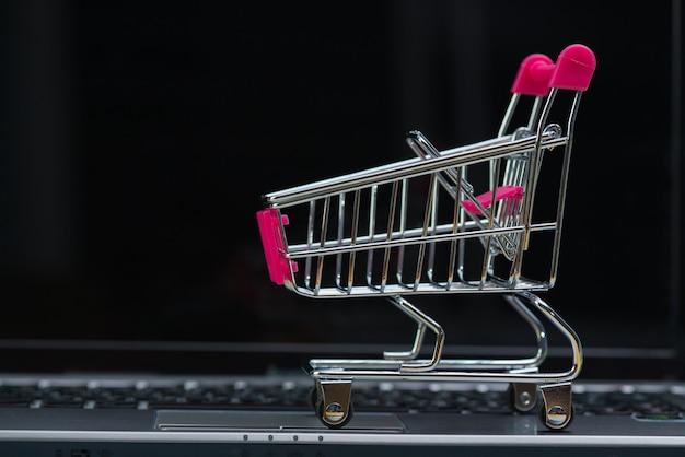 Einkaufswagen- oder supermarktlaufkatze mit laptopnotizbuch, e-commerce und onlineeinkaufskonzept.