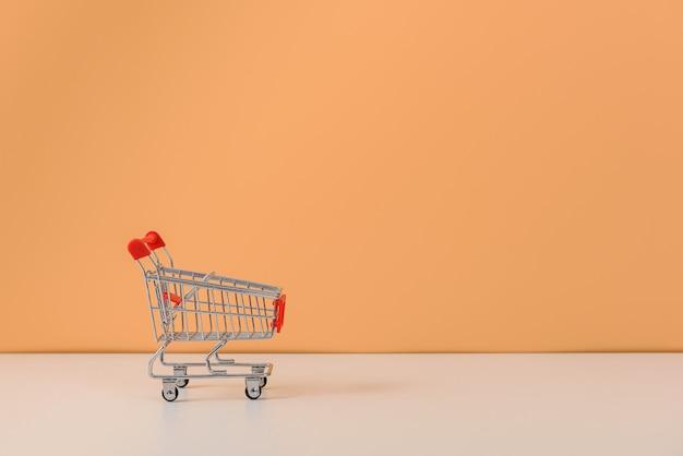 Einkaufswagen oder wagen auf weißem tisch und pastellorange