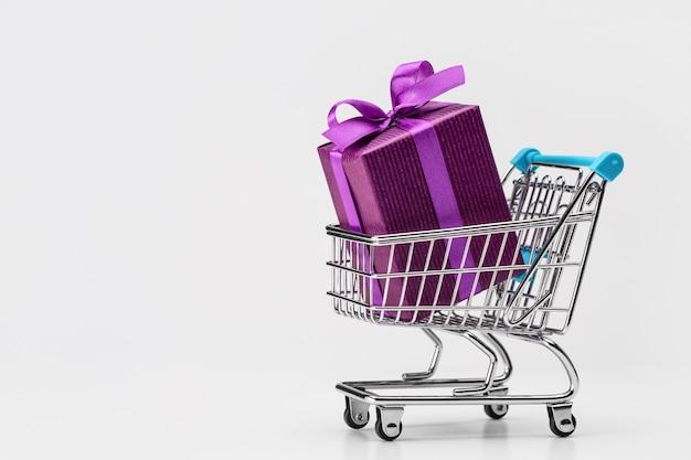 Einkaufswagen (spielzeug) mit geschenken in großer schachtel, verpackt in lila papier. . rabatte, verkauf.
