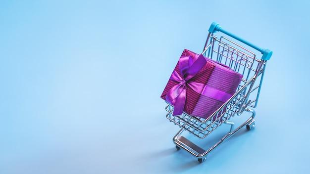 Einkaufswagen (spielzeug) mit geschenken in großer schachtel