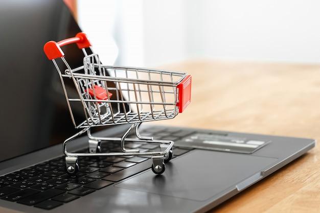 Einkaufswagen und cradit-karte auf laptop im büro.