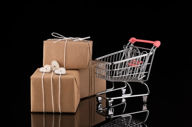 Einkaufswagen und geschenkboxen. kaufen präsentiert konzept, online-shopping. isoliert