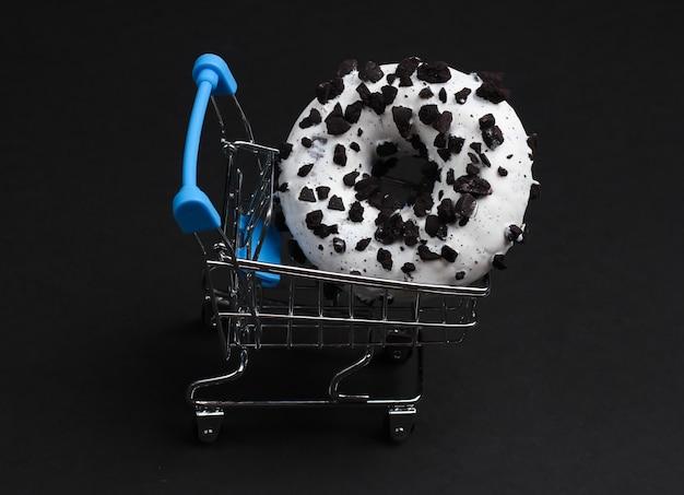 Einkaufswagen und glasierter donut bestreut mit schokoladenstücken auf schwarzem hintergrund. süßigkeiten kuchen, ungesundes essen.