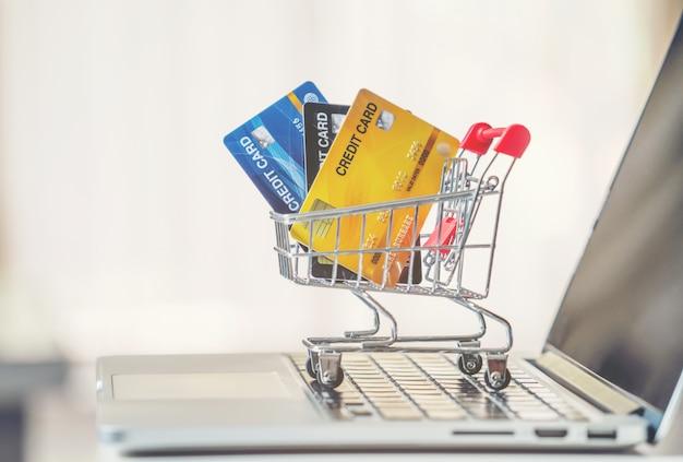Einkaufswagen und kreditkarte mit laptop auf dem schreibtisch