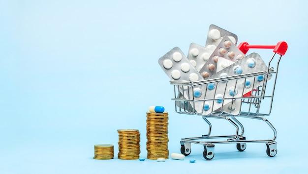 Einkaufswagen und medizin. teure medizin. einkaufskorb mit blasen mit pillen auf blauem grund. stapel von münzen