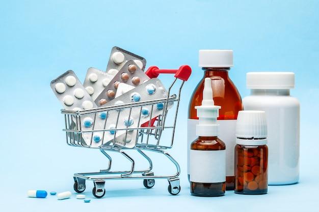 Einkaufswagen und medizin. teure medizin. einkaufskorb mit blisterpackungen mit pillen und medizinflaschen auf blauem grund.