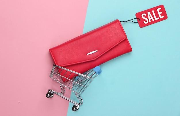 Einkaufswagen und modische lederbrieftasche mit rotem verkaufsetikett auf rosa blau .. rabatt. minimalismus