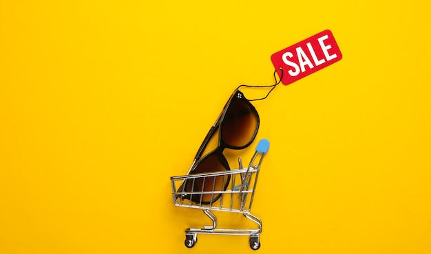 Einkaufswagen und modische sonnenbrille mit rotem verkaufsetikett auf gelb .. rabatt. minimalismus