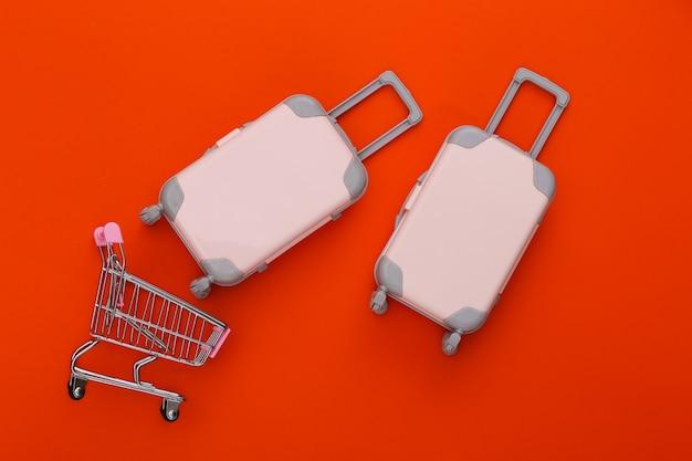 Einkaufswagen und reisegepäck mit zwei spielzeugen, flugzeug und schiff auf orange. reiseplanung