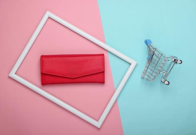 Einkaufswagen und rote lederbrieftasche in einem weißen rahmen auf rosa blauer oberfläche