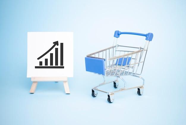 Einkaufswagen und staffelei mit positivem schwarzen trenddiagramm.