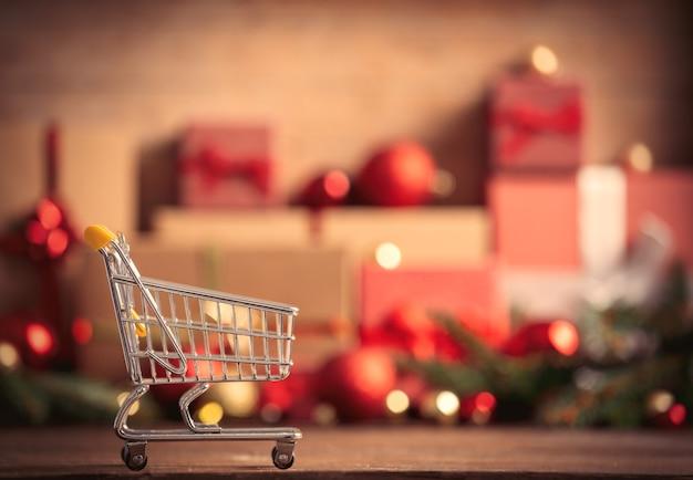 Einkaufswagen und weihnachtsgeschenke auf hintergrund
