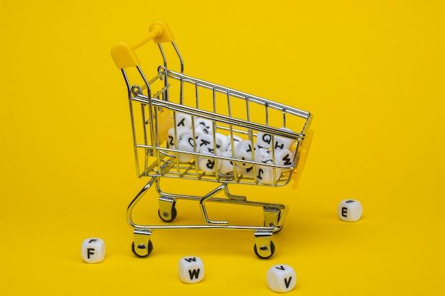 Einkaufswagen und würfel mit buchstaben auf gelbem grund