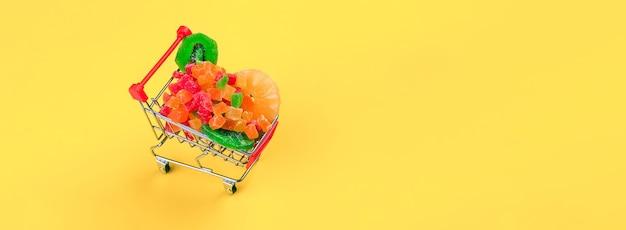 Einkaufswagen voll von bunten farbigen kandierten früchten über gelber wand