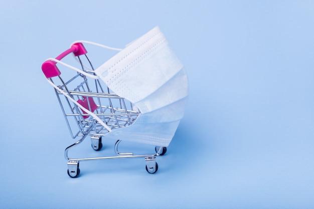 Einkaufswagen zum einkaufen. der wagen trägt eine medizinische maske.