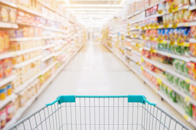 Einkaufswagenansicht im supermarktgang mit abstrakten unscharfen unscharfen hintergrund der produktregale