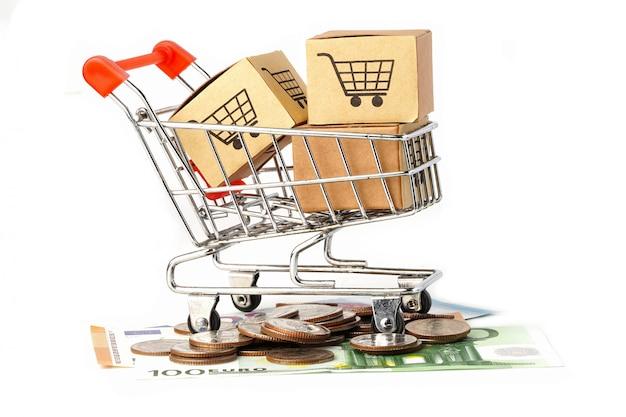 Einkaufswagenkasten auf eurobanknoten und münzen.