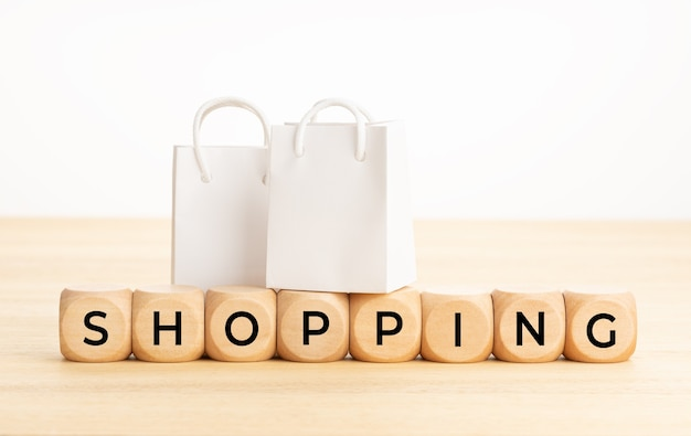 Einkaufswort auf holzklötzen auf tisch- und papiereinkaufstaschen weiße oberfläche kopierraum