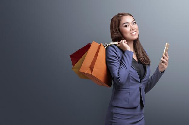 Einkaufszeit, asiatische frau mit dem smartphone, der einkaufstaschen hält