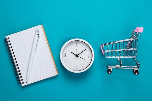 Einkaufszeit. einkaufsliste. supermarktwagen mit uhr, notizbuch auf blauem hintergrund. minimalismus. draufsicht