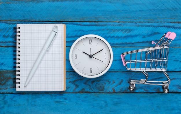 Einkaufszeit. einkaufsliste. supermarktwagen mit uhr, notizbuch auf blauer holzoberfläche. minimalismus. draufsicht