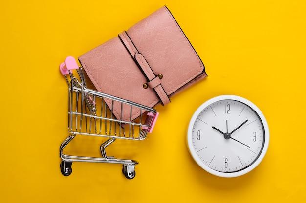 Einkaufszeit. supermarktwagen mit brieftasche, uhr auf gelbem grund. minimalismus. draufsicht