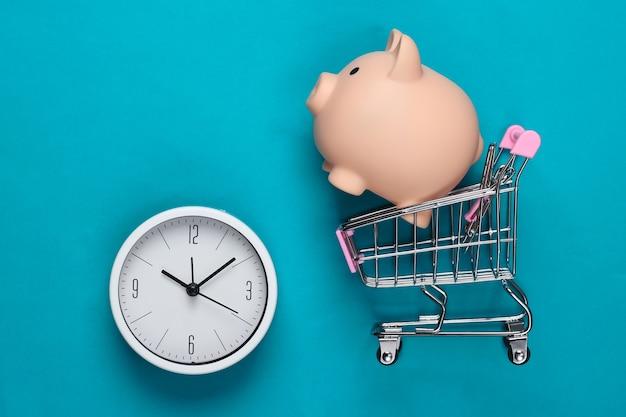 Einkaufszeit. supermarktwagen mit sparschwein, uhr auf blauer oberfläche. minimalismus. draufsicht