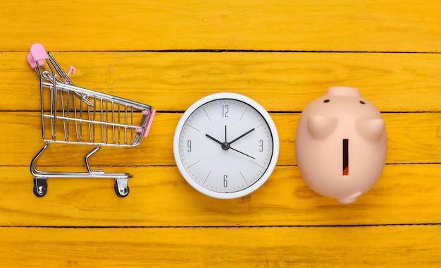 Einkaufszeit. supermarktwagen mit sparschwein, uhr auf gelber holzoberfläche. minimalismus. draufsicht